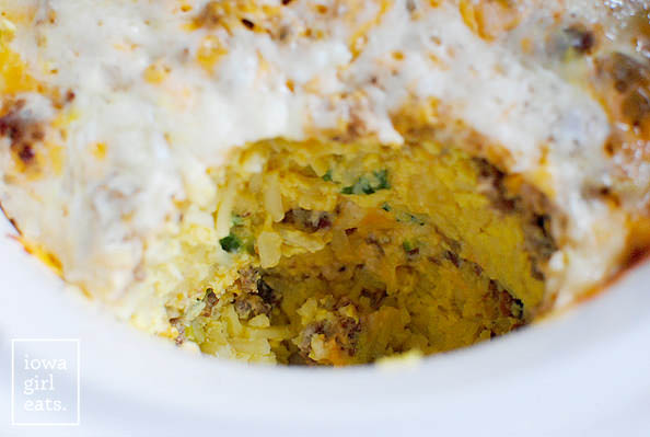 layers of crockpot breakfast casserole with a scoop taken out