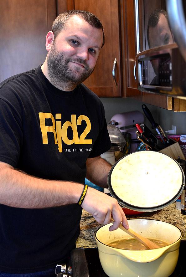 man stirring a pot at the stove