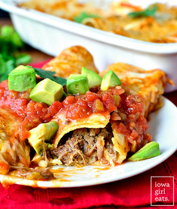 shredded beef enchiladas on a plate with salsa on top