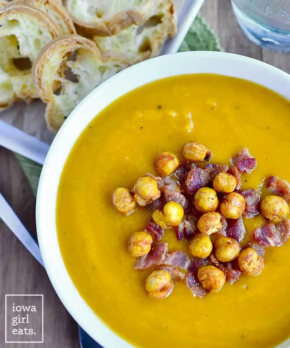 roasted butternut squash soup in a bowl with bacon and crispy chickpeas