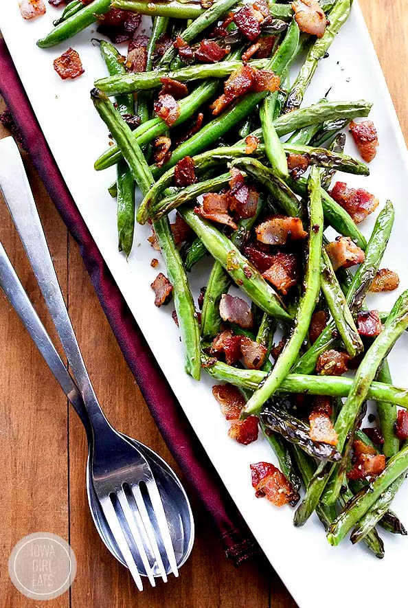 platter of sauted green beans and bacon with a fork