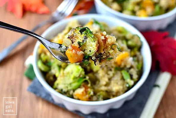 a fork taking a bite of quinoa with caramelized butternut squash and roasted brussels sprouts