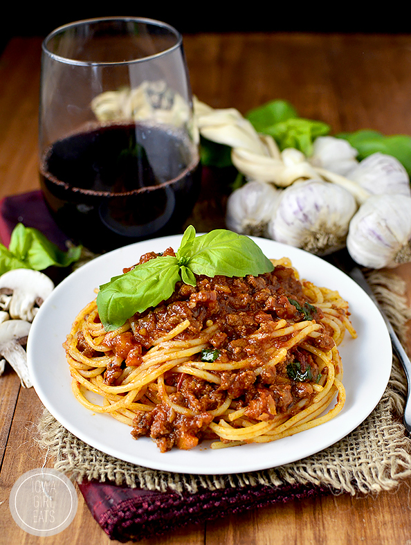 Photo of plate of pasta with ragu sauce and glass of wine