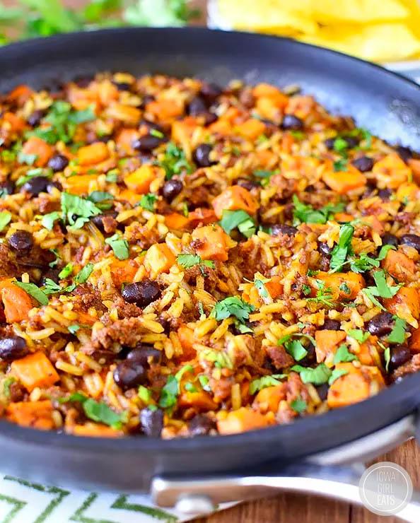 hot skillet full of chorizo black beans sweet potatoes and rice