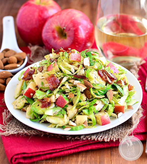 almond bacon brussels sprouts salad on a plate with almonds and apples in the background
