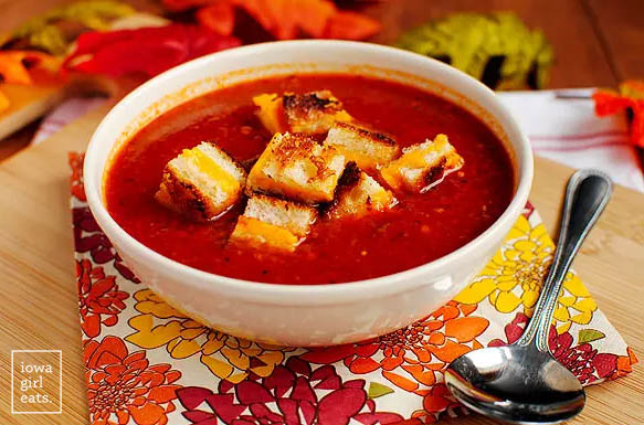 bowl of roasted tomato soup with grilled cheese croutons on top