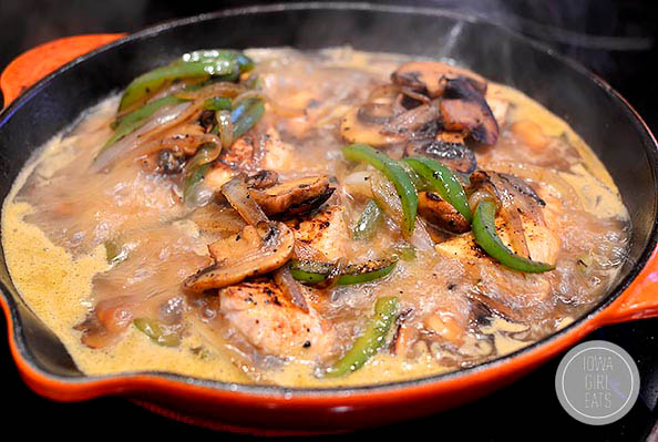 saucy smothered chicken sauting in a skillet
