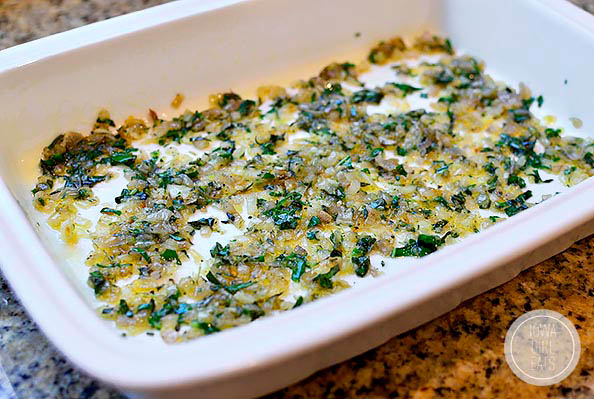 cooked shallots and herbs in the bottom of a baking dish