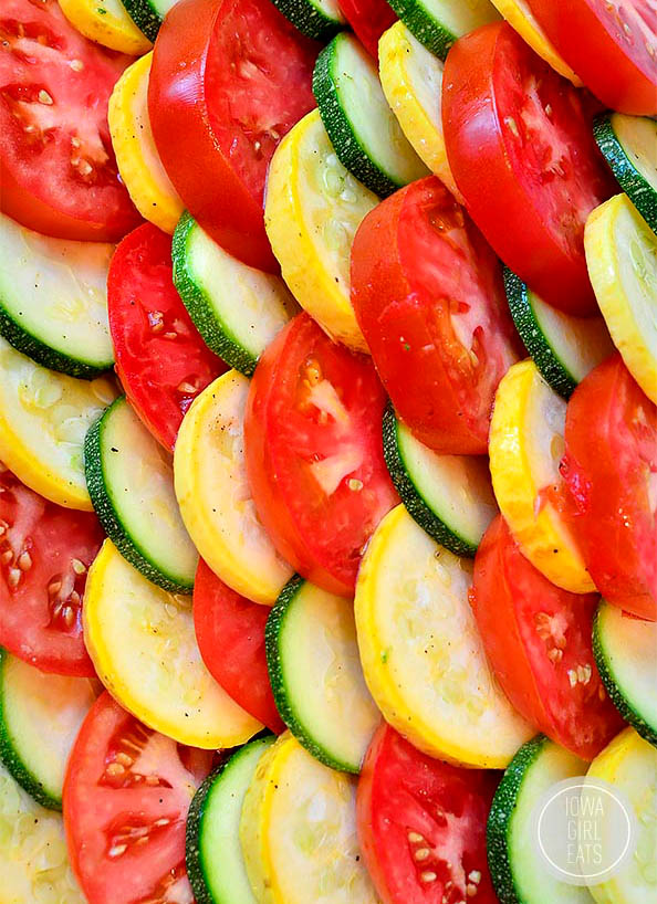 zucchini and summer squash layered with tomatoes in a baking dish