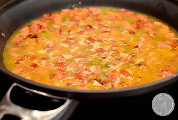 dirty rice ingredients simmering in a skillet