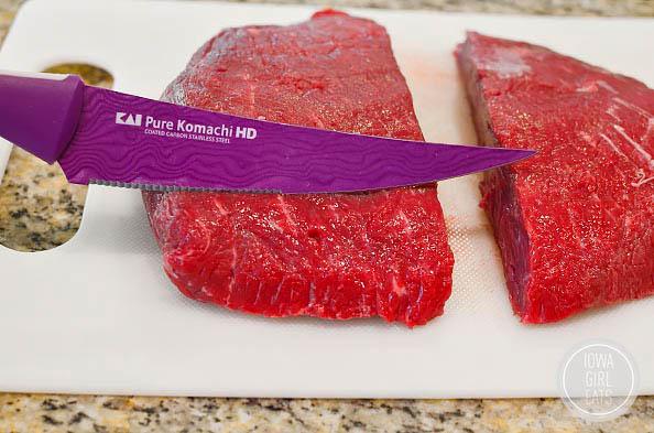 knife cutting steak against the grain