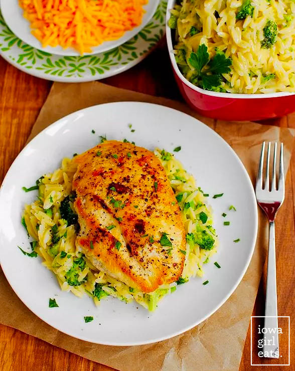 cheesy broccoli orzo on a plate topped with sauteed chicken