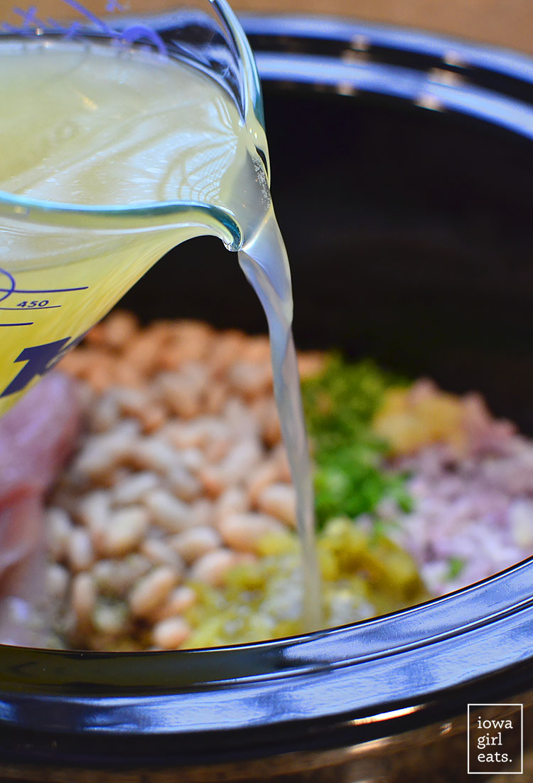 chicken broth being poured into a crock pot with chicken chili ingredients inside