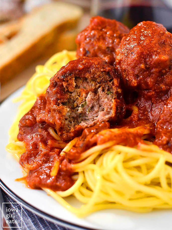 homemade meatball cut in half on a bed of pasta