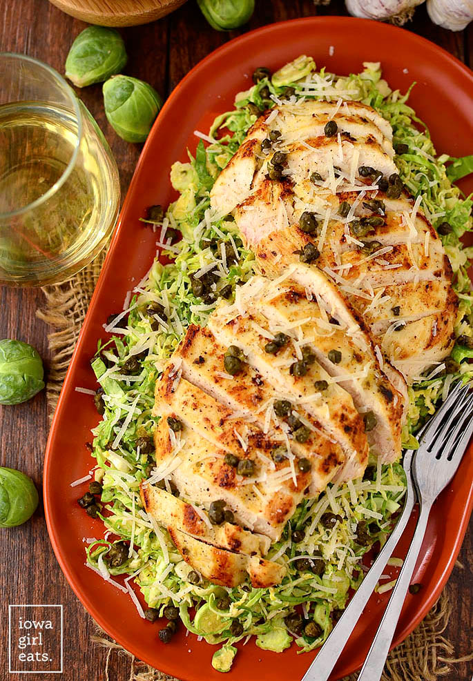 overhead photo of chicken shredded brussels sprout caesar salad with crispy fried capers