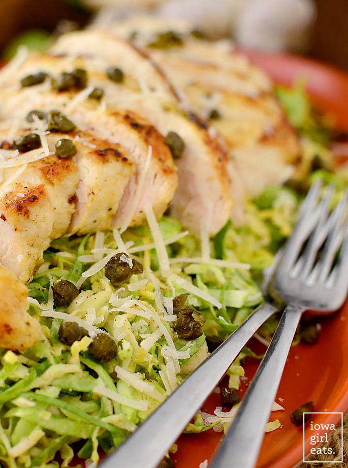 shredded brussels sprout caesar salad on a serving plate with forks