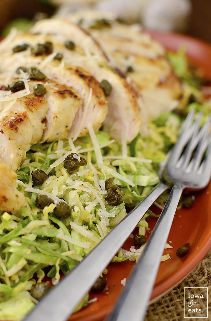 close up photo of healthy caesar salad with chicken and capers