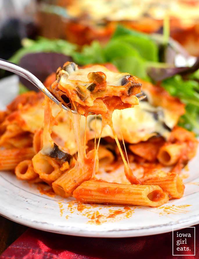 fork taking a cheesy bite of pizza pasta bake