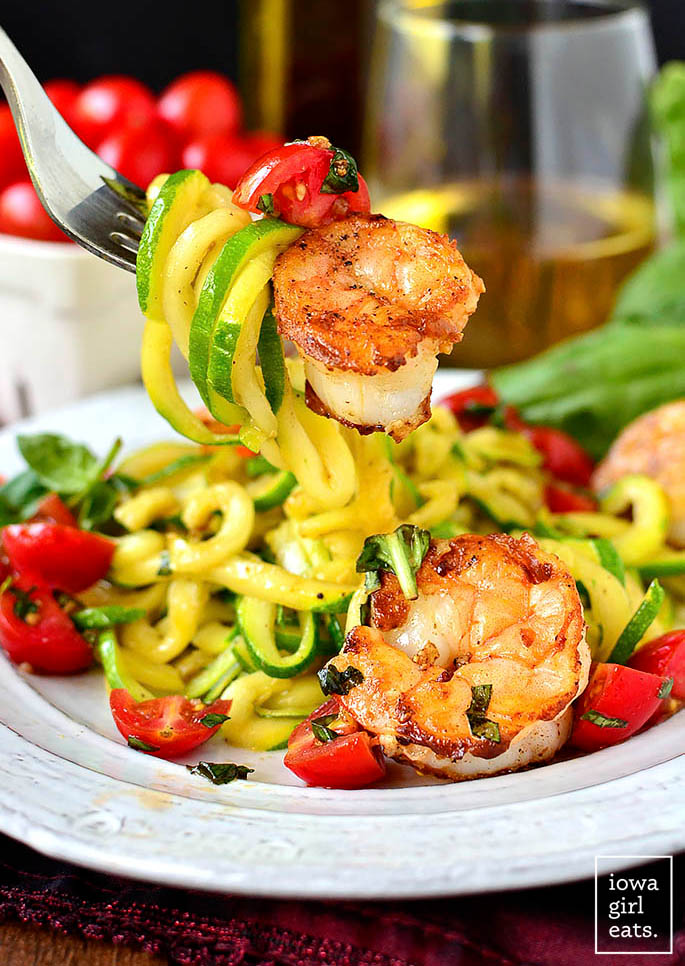 fork digging into zoodles with shrimp tomato and basil