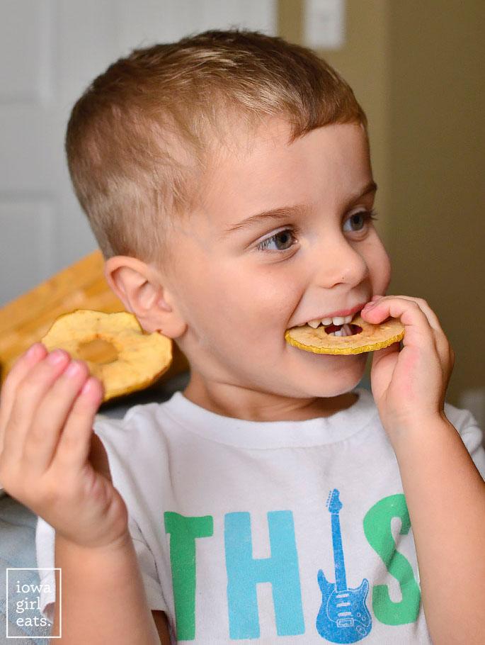 little boy eating baked apple chips