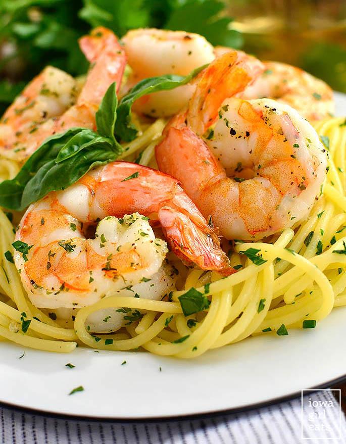roasted shrimp nestled onto a plate of garlic herb butter pasta