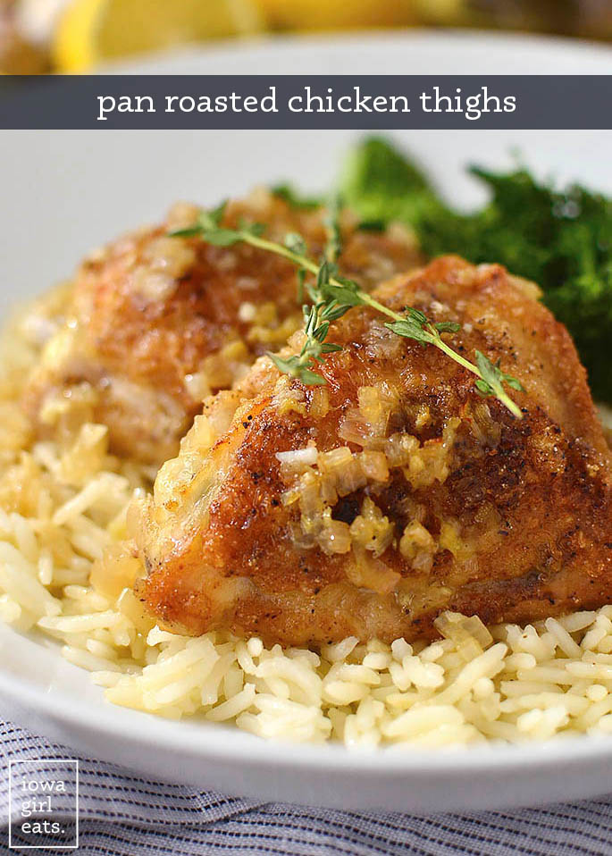pan roasted chicken thighs over rice with a thyme garnish