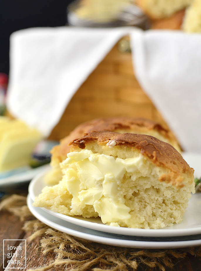 close up photo of half of gluten free dinner roll with butter