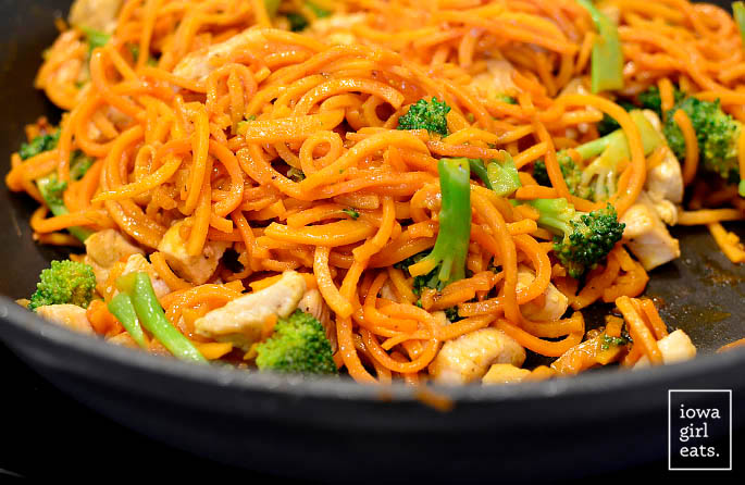 thai peanut chicken sweet potato noodles cooking in a hot skillet
