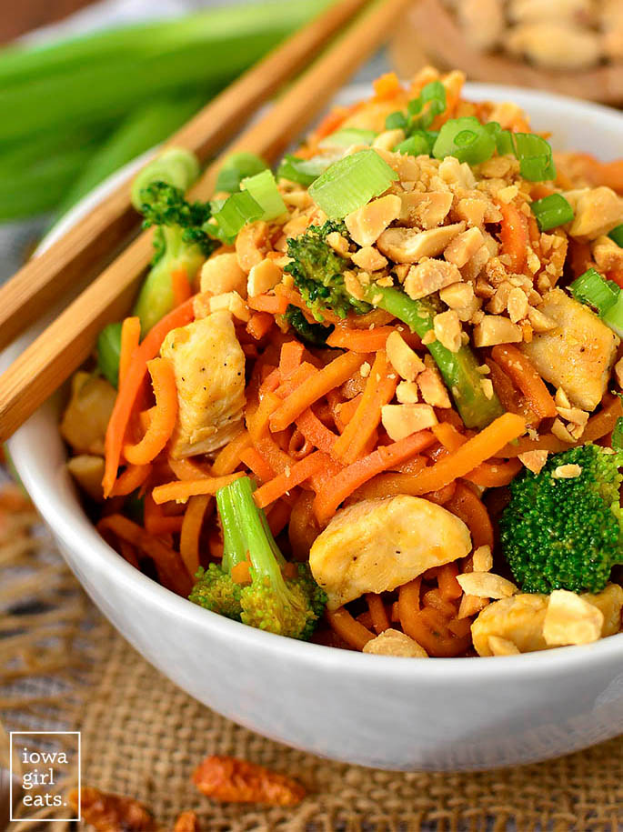 thai peanut chicken sweet potato noodles in a bowl with crushed peanuts