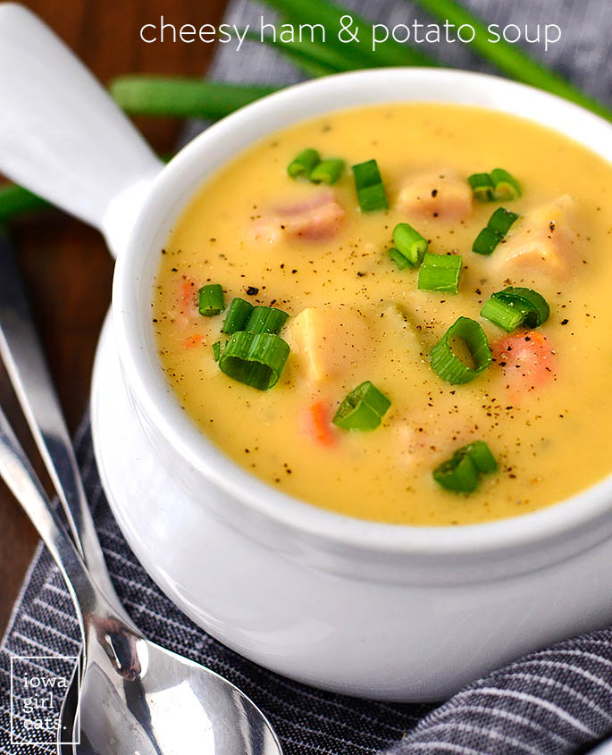 cheesy ham and potato soup in a bowl with sliced green onions