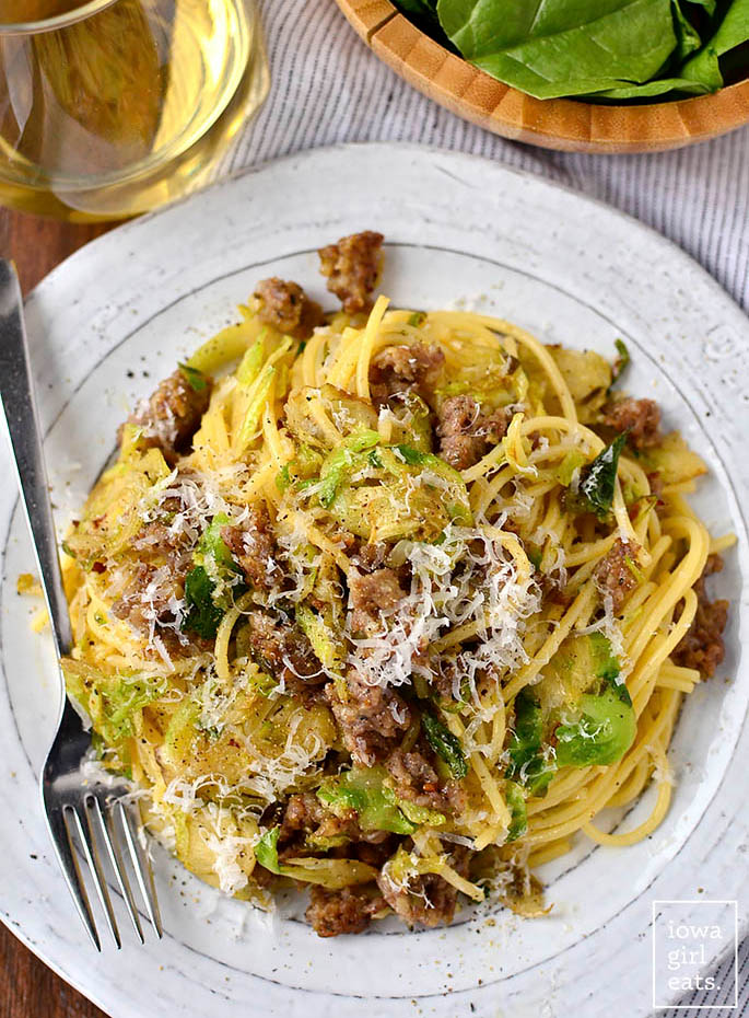 overhead photo of sausage brussels sprouts and parmesan pasta on a plate with a fork