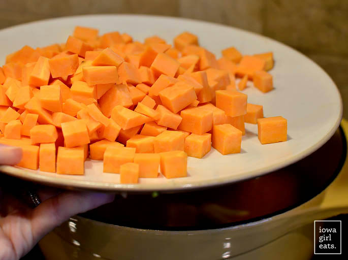 diced sweet potatoes being added to a pot of soup