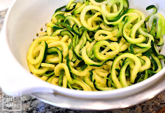zucchini noodles draining in a colander