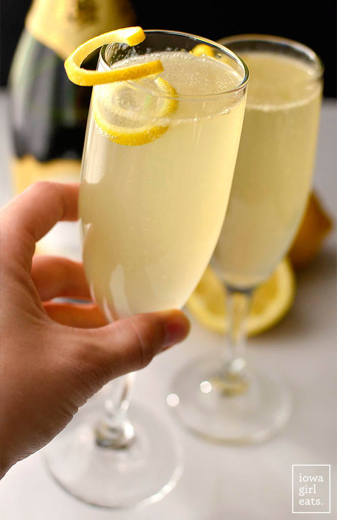 hand cheersing 2 champagne glasses together