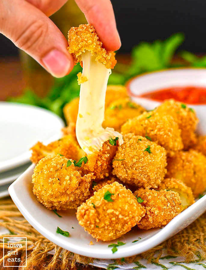 a gluten free mozzarella bite broken in half to show melting cheese