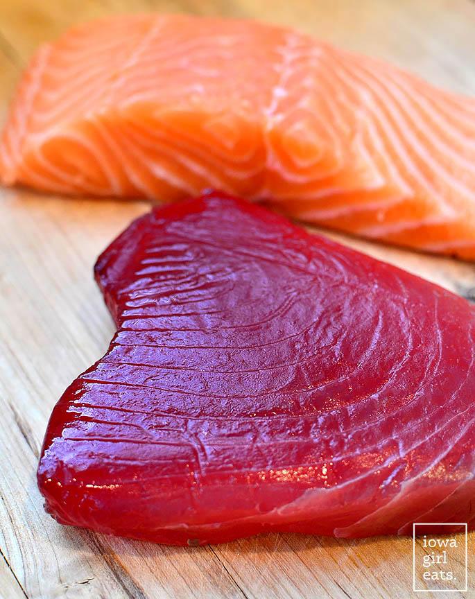 fresh tuna steak and salmon filet on a cutting board