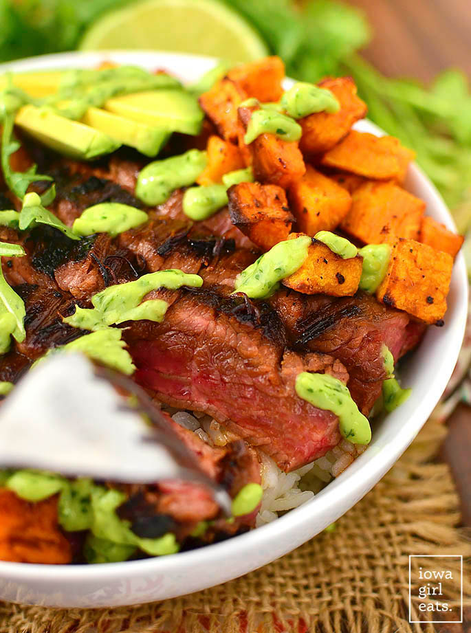 slice of medium rare steak in a bowl with sweet potatoes and avocado