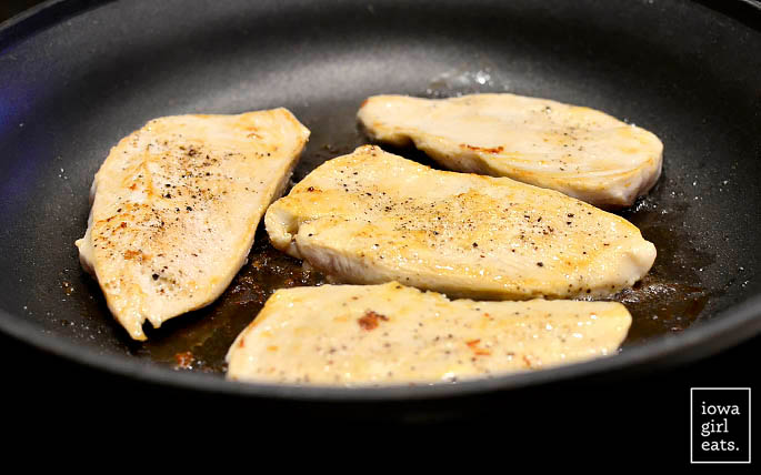 chicken cutlets sauting in a skillet