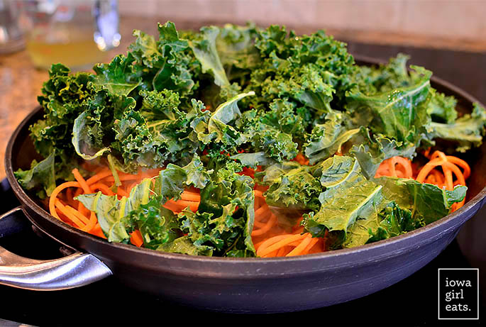 kale and chicken sausage sauting in a skillet