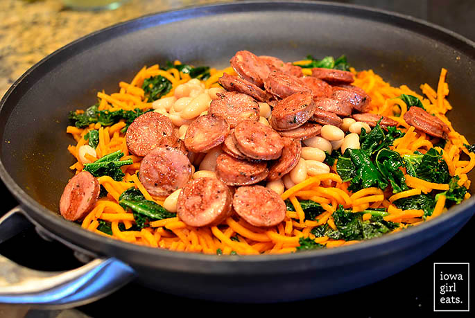 chicken sausage and sweet potato noodles cooking in a skillet