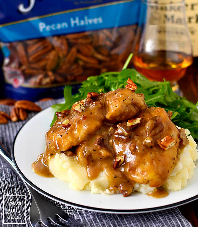 saucey chicken thighs over cooked mashed potatoes on a plate