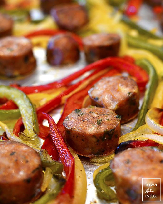 Sheet Pan Sausage and Peppers with Parmesan-Garlic Cauliflower Rice is simple and packed with healthy vegetables. This gluten-free dinner recipe is absolutely delicious! | iowagirleats.com