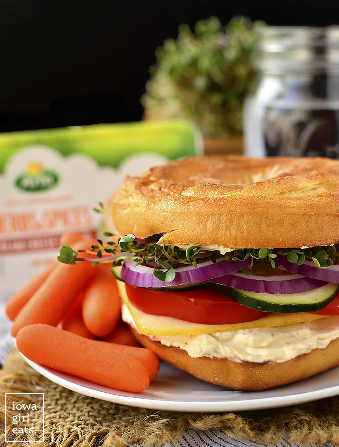 Very Veggie Bagel Sandwich is stuffed with fresh vegetables, herb and spice cream cheese, and mild muenster cheese. A healthy and satisfying breakfast or lunch idea! | iowagirleats.com