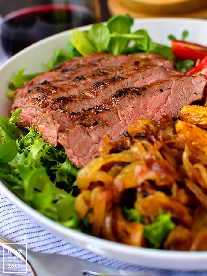 sliced steak on a salad with onions