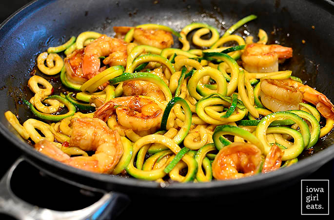 shrimp and zoodles cooking in a hot skillet