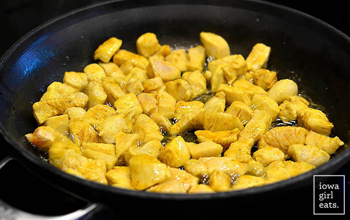 curry seasoned chopped chicken sauting in a skillet