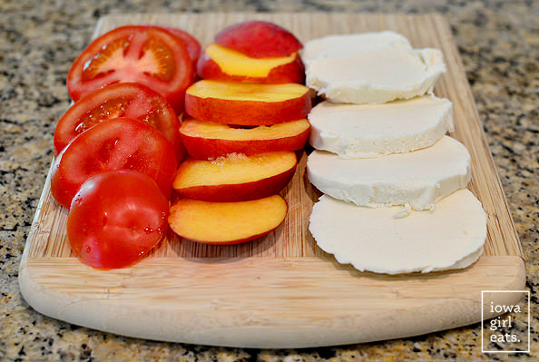 ingredients for a peach caprese salad on a cutting board