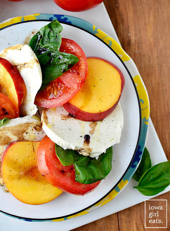 close up photo of a photo of a peach caprese salad on a plate