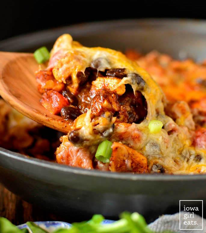 spoon digging into black bean and sweet potato chicken enchilada skillet