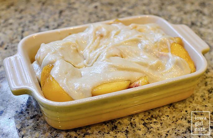 gluten free cobbler topping over fresh peaches in a baking dish